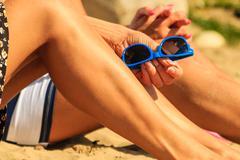 Closeup of women legs sun tanning on beach. - stock photo