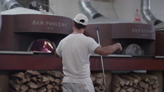 Man adjusts pizzas in an antique stone oven, outdoors. Stock Footage