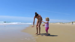 little baby and mother at beach with waves - stock footage