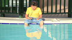 Young boy with  earphone using digital tablet near the pool 3 Stock Footage