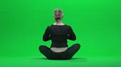 Women meditates against green screen Stock Footage