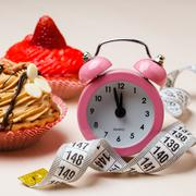 Sweet food measuring tape and clock on table Stock Photos