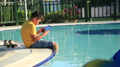 Young boy using digital tablet near the pool 7 Stock Footage