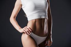 Close up of fit woman's torso with her hands on hips. Female with perfect Stock Photos