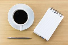 Coffee and notepad on wood table - stock photo