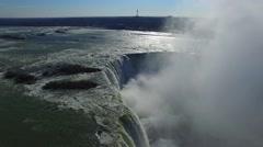 Drone gliding above edge of powerful horseshoe falls in Niagara Stock Footage