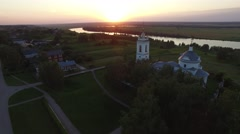Flying around orthodox Church on the river bank at sunset. Aerial view. Stock Footage