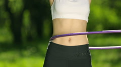 Portrait of beautiful young woman doing hula hoop, outdoors in the park. Woman Stock Footage