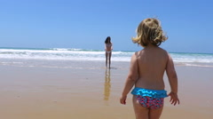 Slow motion baby running towards mother at beach Stock Footage
