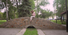 Girl sitting in the park with a computer - stock footage