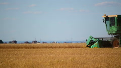 Combine Harvester harvesting in a field of wheat. Slow motion Stock Footage