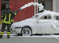 Firemen during exercise to extinguish a fire in a car with foam Kuvituskuvat