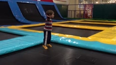 Child jumps on trampoline then runs away Stock Footage