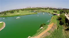 Fly over pond with a fountain in golf course Stock Footage