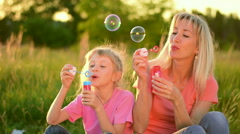 Mother and the child blowing bubbles. Slow motion Stock Footage
