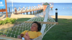 Young boy with earphone listening to music in a hammock Stock Footage
