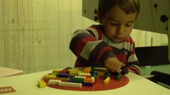 Clever boy builds with constuctional bricks  Stock Footage