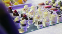 Selection of decorative desserts on a buffet table at a catered luxury event or Stock Footage