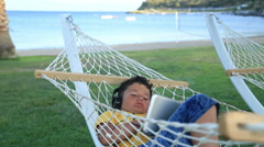 Young boy with earphone using i pad in a hammock Stock Footage