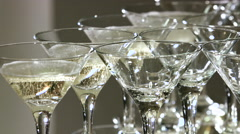 Pouring champagne into a glasses standing on table at the bar in festive evening - stock footage