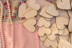 Decorations at a baptism with wooden hearts and necklaces on a table. - stock photo