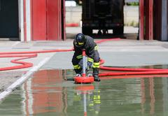 Firefighter positions a powerful fire hydrant during the exercises in the Fir - stock photo