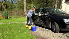 Woman wash black car with soapy sponge Stock Footage