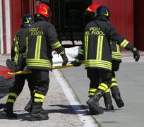 firefighters in action carry a stretcher with injured after car accident - stock photo