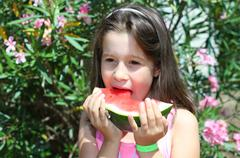cute little girl with brown hair eating a slice of ripe watermelon in summer - stock photo