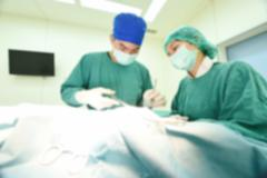 Blur of two veterinarian surgeons in operating room - stock photo