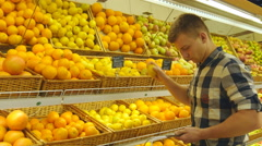 Guy is choosing oranges in supermarket and putting them into shop basket Stock Footage
