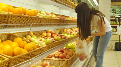 Woman selecting fresh red apples in grocery and putting it in plastic bag Stock Footage