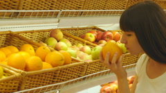 Woman selecting fresh oranges in grocery store and smelling it - stock footage