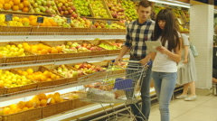 Couple walking in a supermarket with a market trolley and choosing fresh apples Stock Footage