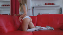 Sexy blonde woman wearing top, thongs and knee socks posing on red leather sofa. - stock footage