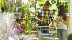 Man is taking and smelling houseplants. Woman is using tablet pc. Stock Footage