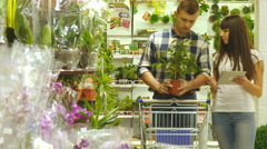 Couple with trolley are walking and choosing indoor plant Stock Footage