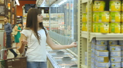Girl coming up to the fridge in shop and taking product from it Stock Footage