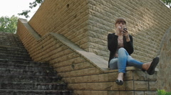 Girl smokes electronic cigarette sitting on the parapet in the park and surfing  Stock Footage