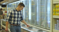 Guy coming up to the fridge in shop and taking product from it Stock Footage