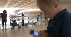 Kid using smart phone in busy shopping centre Stock Footage