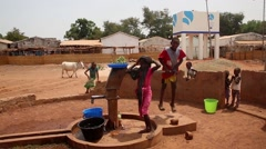 Africa native village children taking water from well Stock Footage