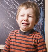 Little cute real boy screaming and crying at school near blackboard close up Stock Photos