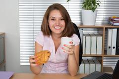 Businesswoman eating at computer In office at work place. Stock Photos