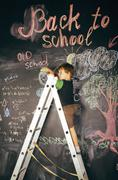 little cute real boy at blackboard in classroom, back to school close up - stock photo
