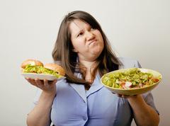 Fat white woman having choice between hamburger and salad close up Stock Photos