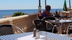 A lady relaxes in a hillside bar overlooking the Atlantic ocean. Stock Footage