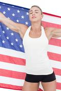 Female athlete holding American flag with closed eyes - stock photo
