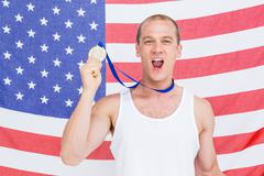 Athlete showing his gold medal in front of american flag - stock photo