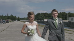 Passionate honeymoon couple, holding hands, walk along the promenade. romantic Stock Footage